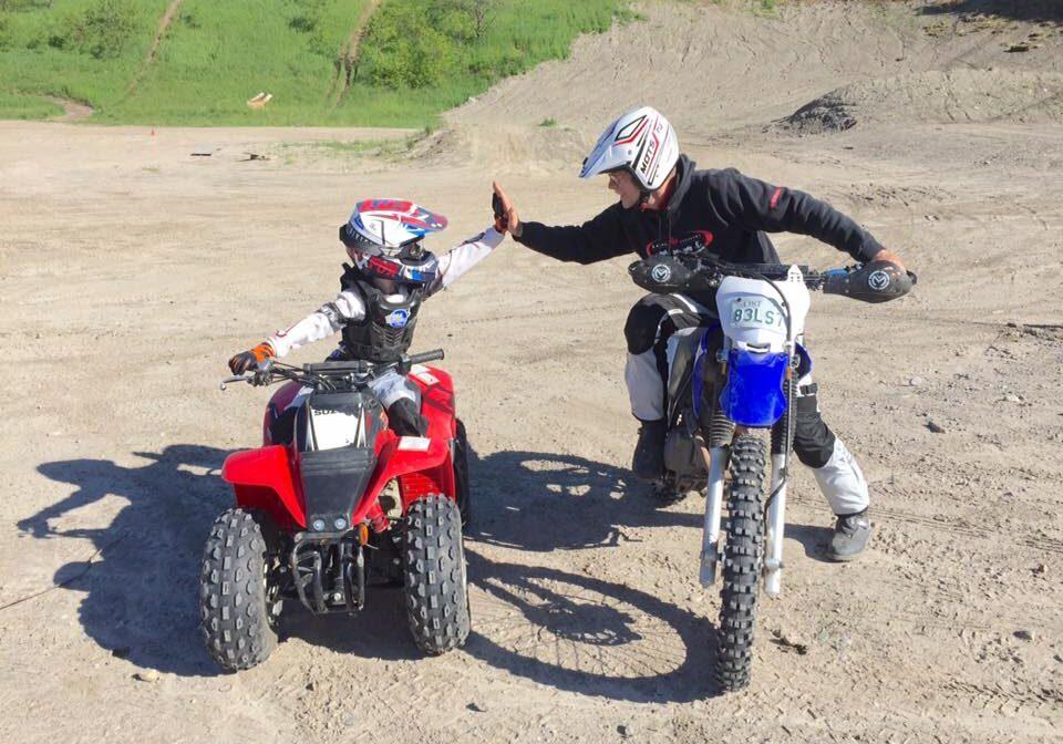 Yamaha Riding Adventures kid on ATV high fives parent